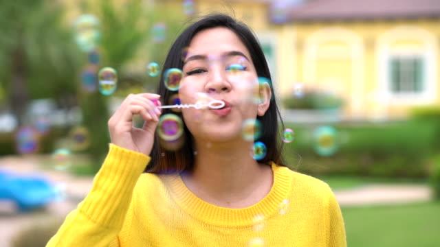 Gerne Asiatin bläst Luftblasen im grünen Garten mit Zeitlupe