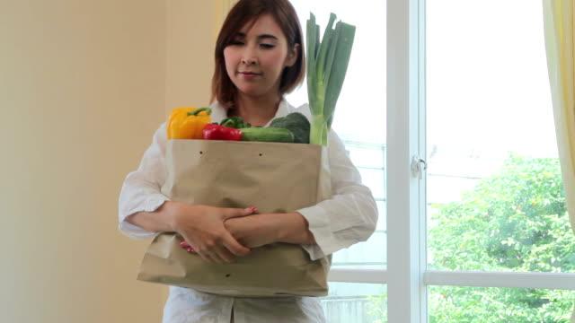 幸せなアジアの女性のキッチンでサラダ野菜を料理 - ジェンダー・ステレオタイプ点の映像素材/bロール