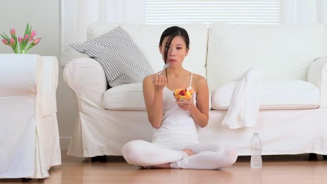 Happy Asian woman eating fruit