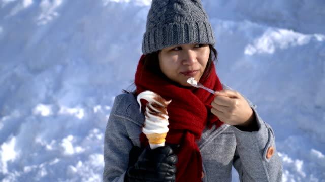 北海道小樽市で雪の中でアイスクリームを食べて幸せなアジア女