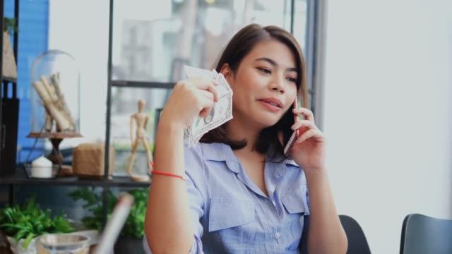glückliche asiatische frau hält dollar und telefonieren im café. - arbeit und beschäftigung stock-videos und b-roll-filmmaterial