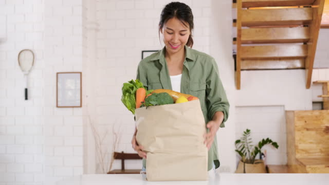 vídeos de stock e filmes b-roll de happy asian woman  holding vegetable bag walking into kitchen after shopping at grocery store at home.vegan lifestyle concept - saco objeto manufaturado