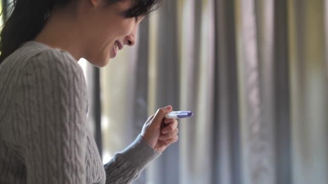 vídeos de stock, filmes e b-roll de a mulher asiática feliz está grávida usando o teste de gravidez - segurar