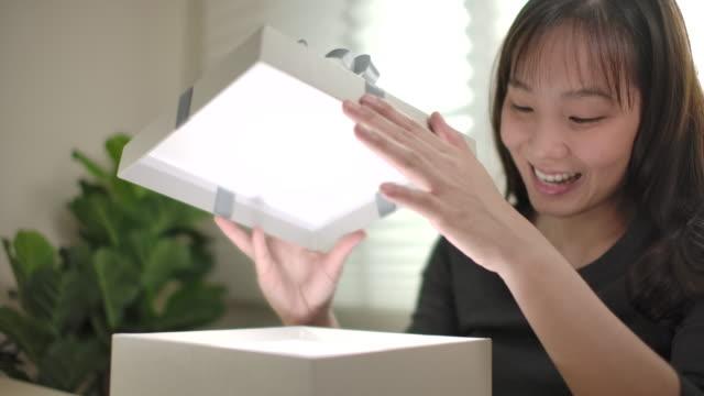 glückliche asiatische frau öffnen gift box zu hause - bildkomposition und technik stock-videos und b-roll-filmmaterial