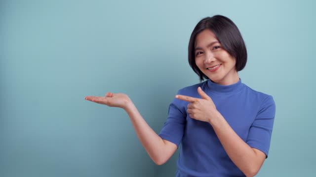 幸せなアジアの女性は、青い背景に分離されたコピースペースを提示します。4kビデオ - 問う点の映像素材/bロール