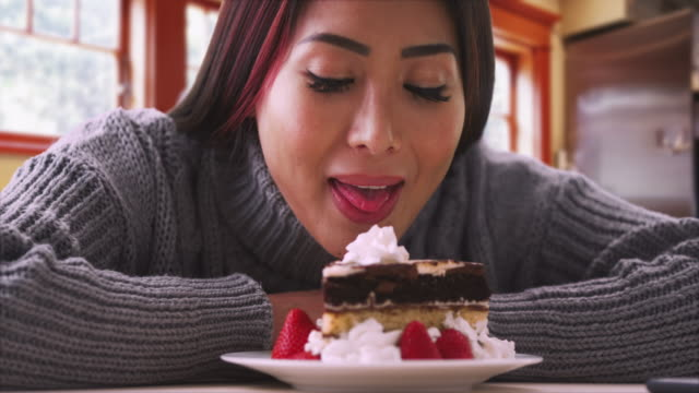 Happy Asian woman smiling with cake at home