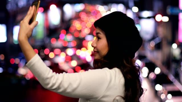 Happy asian woman taking selfie joyful and happy smiling at night