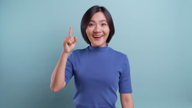 happy asian woman thinking and having an idea  isolated over blue background 4k video - human head stock videos & royalty-free footage