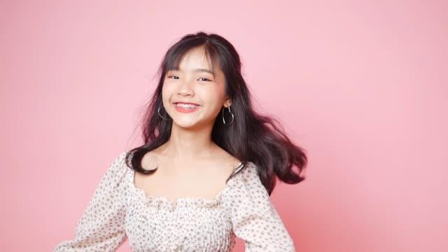 vídeos y material grabado en eventos de stock de feliz mujer asiática dando vueltas en el fondo rosa, cámara lenta. - miembro humano