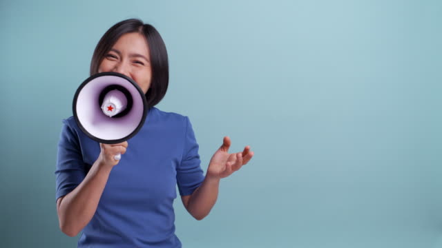 happy asian woman used megaphone making shout gesture isolated on blue background. 4k video - speech stock videos & royalty-free footage