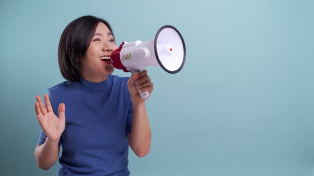 happy asian woman used megaphone making shout gesture isolated on blue background. 4k video - megaphone stock videos & royalty-free footage