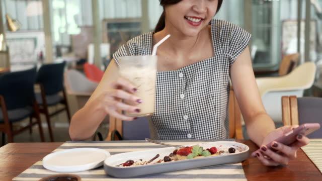 Glad asiatisk kvinna med vackert leende njuta av att äta choklad kaka dessert i coffee shop och kul med Online Shopping på mobiltelefon