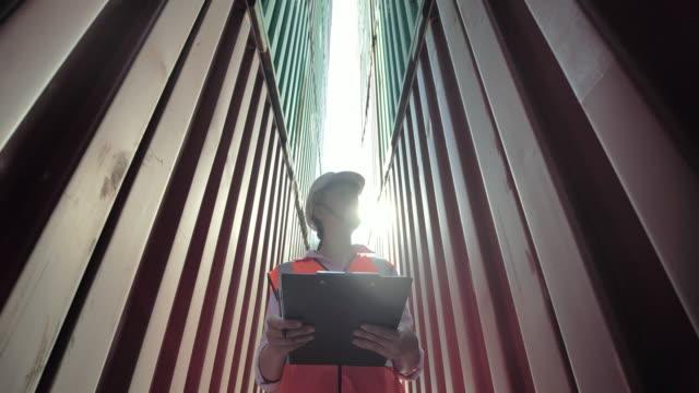 glückliche asiatische frauen ingenieur steuerung ladebehälter box aus fracht. liefer-, handels-, wachstums-, connection-, kommunikations-, business-, empowerment-, leadership-, frauen-in-mint-, industrie- und transportkonzept. frachtcontainer - klemmbrett stock-videos und b-roll-filmmaterial