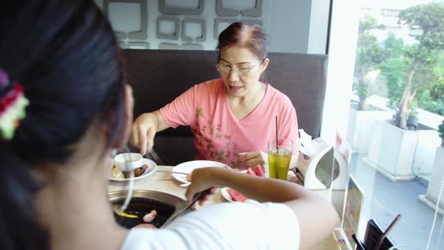 ホットコールストーブでバーベキューポークを焼く幸せなアジアの女性。韓国または日本のバーベキュースタイル。 - ソース点の映像素材/bロール