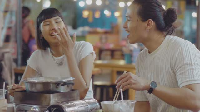 vídeos y material grabado en eventos de stock de feliz asiático joven grupo comiendo shabu shabu en el restaurante en el mercado nocturno. - coreano oriental