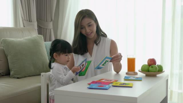 vídeos de stock, filmes e b-roll de matriz e filha novas asiáticas felizes que jogam com cartão do alfabeto, instrução adiantada em casa. - texto