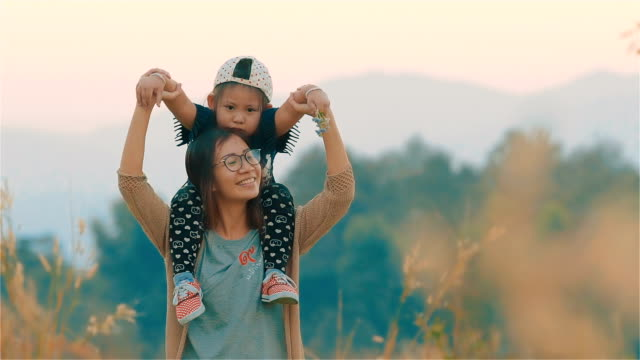 Happy Asian young mother carrying her daughter on her shoulder in the blurred field together