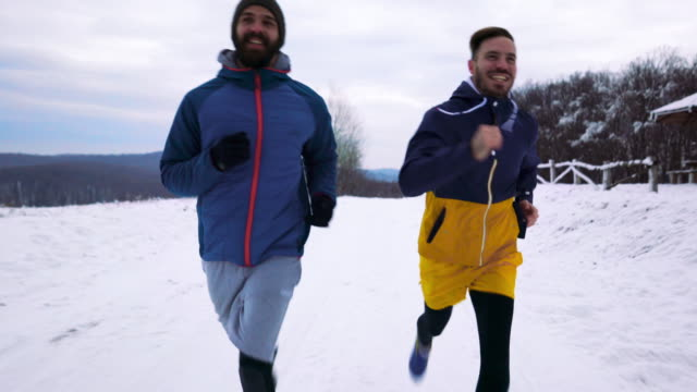 happy athletic men running on a snow in the park. - body concern stock videos & royalty-free footage
