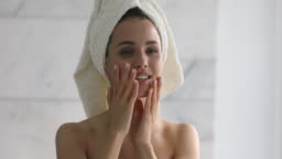 Happy attractive young woman with towel on head touching face