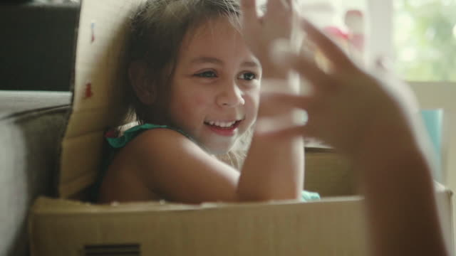 Happy baby and her sister playing in cardboard box.