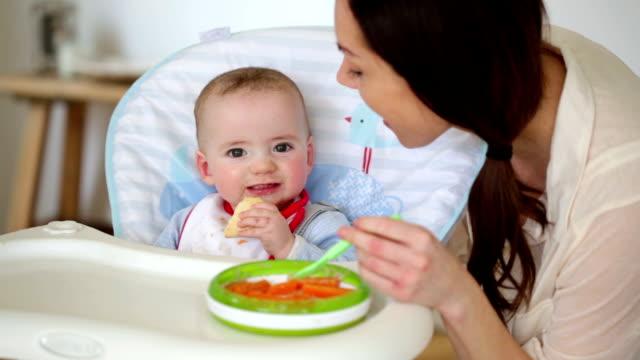 vídeos de stock, filmes e b-roll de bebê feliz a ser alimentada por mãe - comida de bebê