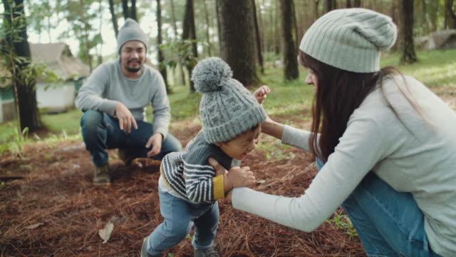 フォレスト内の芝生の上の彼の最初のステップを作る幸せな男の子。 - 両親点の映像素材/bロール