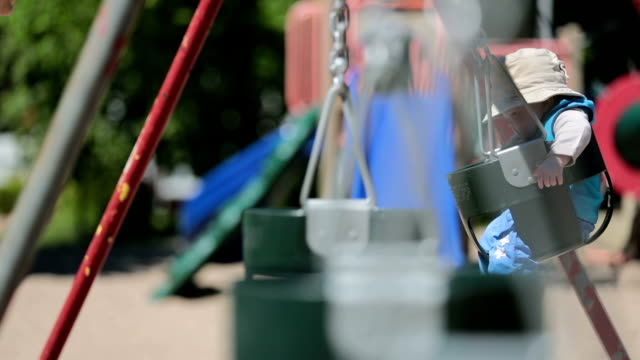 happy baby boy sitting in playground swing outdoors with mom - swinging stock videos & royalty-free footage