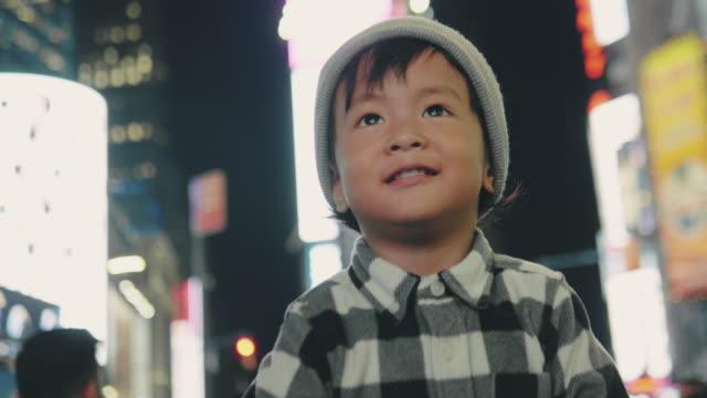 glückliches baby boy lächelnd in der stadt bei nacht - plakatwand stock-videos und b-roll-filmmaterial