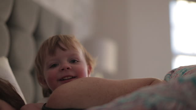 happy baby boy waking up his mother - differential focus stock videos & royalty-free footage