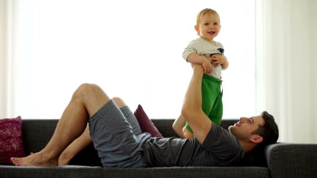 happy baby boy with dad on couch - genderblend stock videos & royalty-free footage