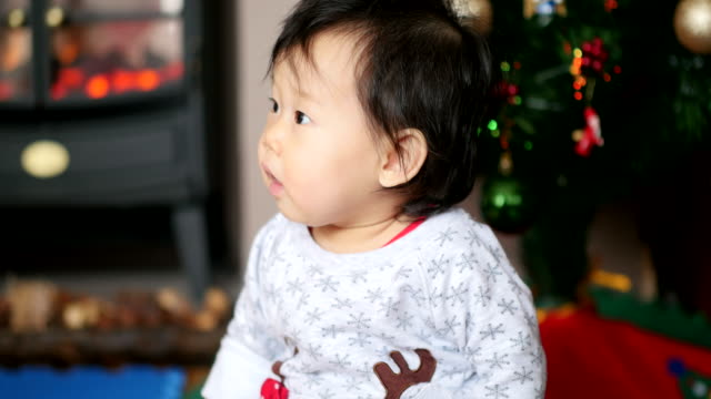happy baby girl wearing christmas jumper at home - one baby girl only stock videos & royalty-free footage