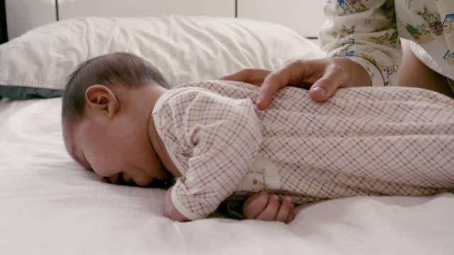 vidéos et rushes de relaxation heureuse de nouveau-né de chéri sur le lit - 2 5 mois