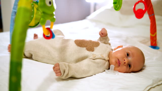 glückliches baby in baby gym spielzeug spielen - ein männliches baby allein stock-videos und b-roll-filmmaterial