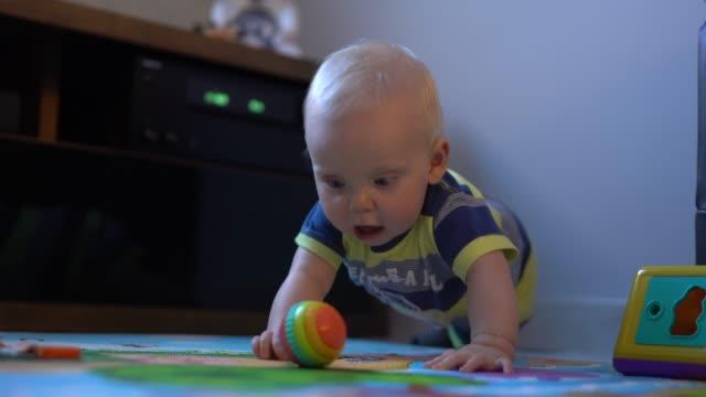 vídeos de stock, filmes e b-roll de bebê feliz que joga com os brinquedos na sala de visitas - babies only