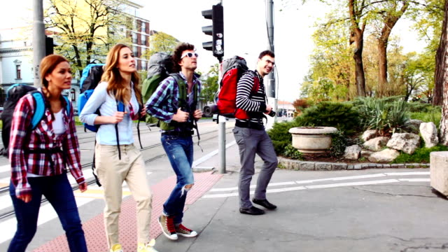 hd: happy backpackers crossing the street. - neighborhood street sign stock videos and b-roll footage