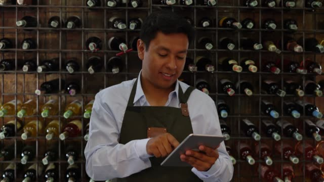 happy bartender making a wine inventory on tablet while facing camera smiling - bar drink establishment stock videos and b-roll footage
