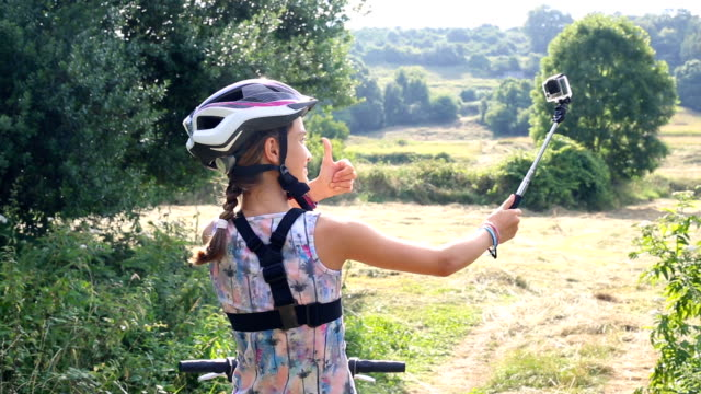 Happy bblond girl, preteen, with helmet and braid doing a selfie on a bicycle in nature