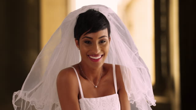 Happy beautiful bride lifts away her veil, laughing and excited