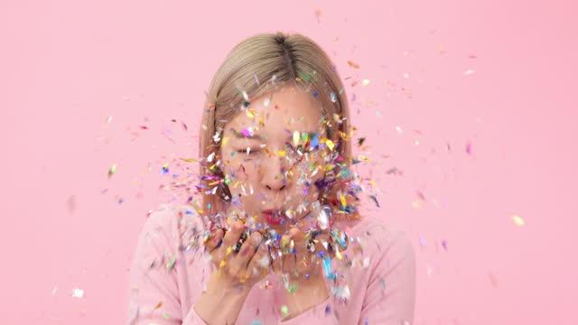 glückliche schöne frau bläst konfetti auf rosa hintergrund. - ostasiatischer abstammung stock-videos und b-roll-filmmaterial