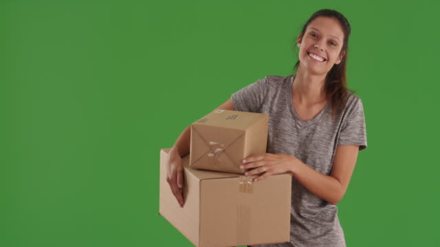 stockvideo's en b-roll-footage met happy beautiful woman carrying shipping boxes with big smile on greenscreen - charmant