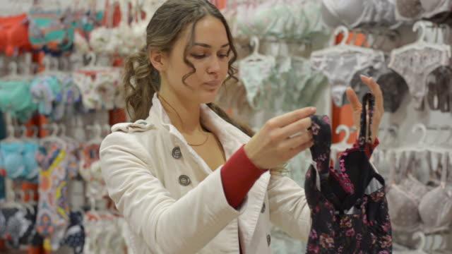 vidéos et rushes de heureuse belle femme en lingerie magasin - lingerie féminine