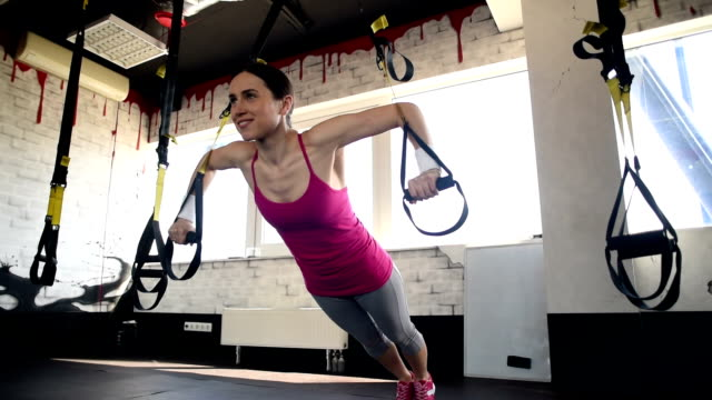 happy beautiful woman is  training with the trx straps. - rope stock videos & royalty-free footage