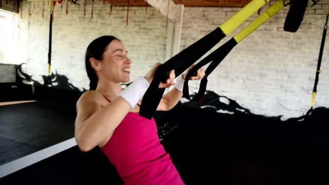 happy beautiful woman is  training with the TRX straps.