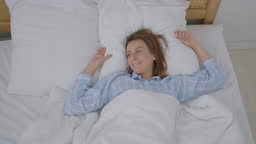 Happy beautiful woman wake up, smiling and stretching her arms in her bed in the bedroom. Young female use relax time at home. Lifestyle woman at home concept.