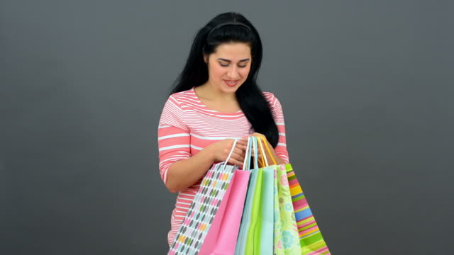 happy beautiful woman with shopping bags on the grey background. - financial item stock videos & royalty-free footage