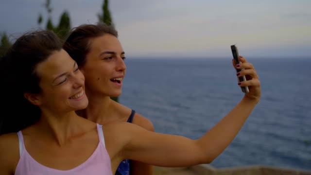 happy best friends girls make selfie picture on camera behind sunrise sky - cinemanis videography stock videos & royalty-free footage
