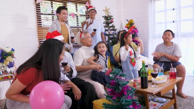 glückliche große asiatische familie genießen tanzen und feiern weihnachten zusammen im wohnzimmer zu hause - kopfbedeckung stock-videos und b-roll-filmmaterial