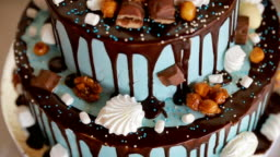 Happy Birthday cake. Child first birthday party. Chocolate icing cake decorated with different candies and toy doll on it
