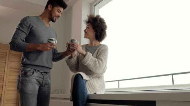 vídeos de stock, filmes e b-roll de casal negro feliz desfrutando em seu tempo de café pela janela e se comunicando. - xícara de café