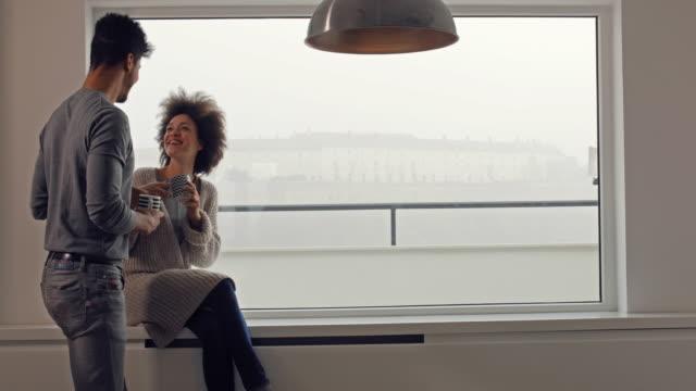 vídeos de stock, filmes e b-roll de feliz casal negro apaixonado desfrutando o tempo do café pela janela. - xícara de café